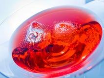 Конец-вверх красного питья коктеиля с кубами льда на голубых светлых предпосылке подкраской, потехе и диско танца Стоковая Фотография