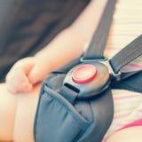 Конец-вверх красной кнопки с рукой младенца Стоковые Изображения RF