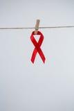 Конец-вверх красной смертной казни через повешение ленты осведомленности СПИДА от зажимки для белья на строке Стоковое фото RF