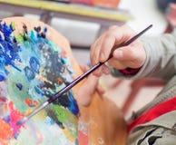 Конец вверх красок смешивания руки ` s человека с щеткой в изображении натюрморта палитры и картины на холсте в студии художника Стоковая Фотография RF