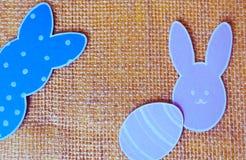 Конец-вверх красочных бумажных рамок кролика и бумажных яичка силуэта против предпосылки холста Стоковые Изображения RF
