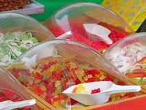 Конец вверх красочных камедеобразных помадок носит в рынке с белыми пластичными ветроуловителями стоковое фото rf