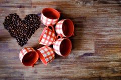 Конец-вверх красочных чашек и сердца от кофейных зерен Стоковые Фотографии RF