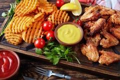 Конец-вверх крылов жареной курицы, фраев картошки Стоковые Фото