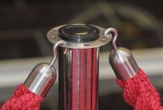 Конец вверх крюков нося красный барьер входа ropes Стоковые Фото