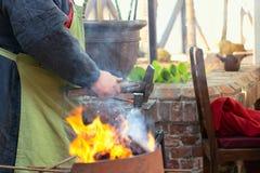 Конец-вверх кузнеца вручную куя расплавленный метал на наковальне в мастерской кузницы Стоковая Фотография RF