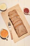 Конец-вверх куска хлеба здравицы с вареньем и маслом на деревянной плате Стоковая Фотография