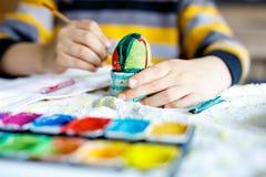 Конец-вверх маленького ребенка вручает яичка расцветки на праздник пасхи стоковые фото