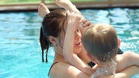 Конец-вверх маленького ребенка имея потеху в бассейне с его мамой, замедленное движение видеоматериал