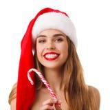 Конец-вверх маленькой девочки, блондинка, шляпа santa, при леденец на палочке сформированный как тросточка, изолированная на бело стоковое фото rf