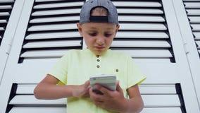 Конец-вверх мальчика используя мобильный телефон пока играющ игры Портрет использования футболки красивого мальчика нося умен видеоматериал
