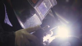 Конец-вверх маски сварщика пока сваривающ зажим Сварщик сваривает части структуры сток-видео
