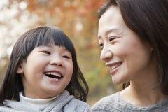 Конец-вверх матери и дочери смеясь над в парке, осени, Китая Стоковое Изображение