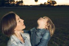 Конец-вверх матери обнимая ее маленькую дочь на заходе солнца стоковое изображение