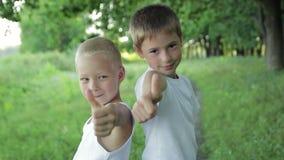 Конец-вверх 2 мальчиков показывает большой палец руки сток-видео