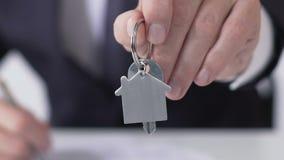 Конец-вверх менеджера компании держа ключи квартиры, строя дело приобретения сток-видео