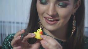 Конец-вверх меньшей желтой резиновой утки в руках модели видеоматериал