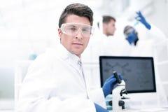конец вверх микробиолог ученого на таблице лаборатории стоковая фотография