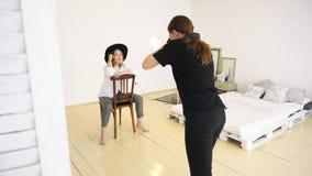 Конец-вверх молодого женского фотографа в черных одеждах принимая pfotos стильной молодой женщины в черной шляпе, белой рубашке сток-видео