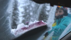 Конец вверх молодого человека лыжника чистит снег щеткой от припаркованного автомобиля в лыжном курорте зимы Стоковая Фотография