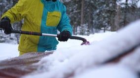 Конец вверх молодого человека лыжника чистит снег щеткой от припаркованного автомобиля в зиме Стоковые Изображения RF