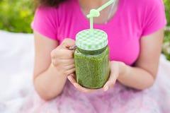Конец-вверх молодой женщины держа зеленые smoothies на пикнике Здоровые еда, вытрезвитель и концепция диеты Стоковое Изображение RF