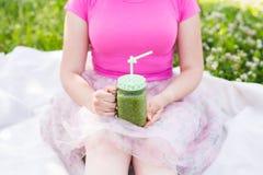 Конец-вверх молодой женщины держа зеленые smoothies на пикнике Здоровые еда, вытрезвитель и концепция диеты Стоковые Изображения