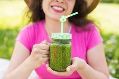 Конец вверх молодой женщины имеет потеху в парке и выпивает зеленые smoothies на пикнике Стоковое Изображение RF