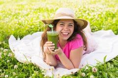 Конец вверх молодой женщины имеет потеху в парке и выпивает зеленые smoothies на пикнике Стоковая Фотография
