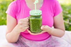 Конец вверх молодой женщины имеет потеху в парке и выпивает зеленые smoothies на пикнике Стоковое Фото