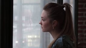 Конец-вверх молодой унылой женщины смотря вне окно сток-видео