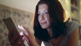 Конец-вверх молодой усмехаясь женщины используя smartphone лежа в кровати дома на ноче Стоковое Изображение RF