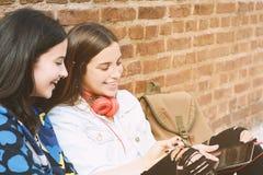 Конец-вверх 2 молодых красивых друз женщин используя цифровую таблетку Стоковое фото RF