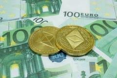 Конец-вверх 2 монеток Ethereum на 100 банкнотах евро Секретная валюта ETC стоковая фотография