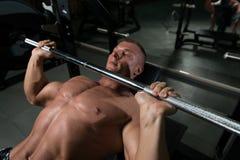 Конец-Вверх молодого человека в спортзале работая комод на стенде Pre Стоковые Фото