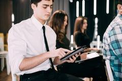 Конец вверх молодого человека с таблеткой делает извещение на представлении или встрече команды офиса Сыгранность Стоковое фото RF