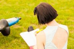 Конец-вверх молодой задней части женщины с велосипедом и книгой Стоковое Изображение