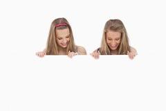 Конец-вверх 2 молодых женщин держа пустую доску Стоковое Фото