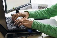 Конец-вверх мужских рук над черной клавиатурой компьтер-книжки во время печатать стоковое фото