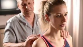 Конец-вверх мужских рук физиотерапевта делая массаж здоровья к пациенту маленькой девочки Osteopathy и не традиционное акции видеоматериалы