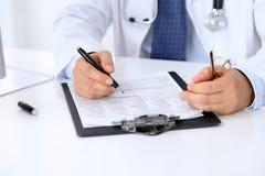 Конец вверх мужского доктора сидит на таблице и заполняет вверх по форме истории болезни Стоковые Изображения