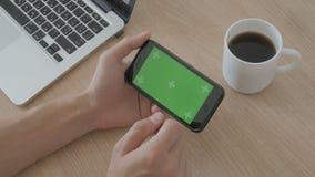 Конец-вверх мужской касаться рук smartphone на таблице рабочего места Зеленый ключ Chroma экрана сток-видео