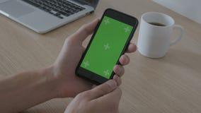 Конец-вверх мужской касаться рук smartphone на таблице рабочего места Зеленый ключ Chroma экрана видеоматериал