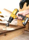 Конец-вверх мужской руки и желтой отвертки Человек делает большое отверстие в доске с особенным инструментом стоковое фото rf