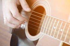 Конец-вверх мужской руки комплектуя строки гитары стоковые фотографии rf