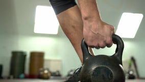 Конец-вверх - мужской спортсмен поднимая Kettlebell в спортзале сток-видео