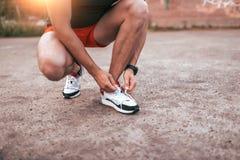 Конец-вверх, мужской спортсмен, связывая шнурки на тапках Концепция утра jogging в городе Загоренный кожаный, умный дозор стоковые фотографии rf