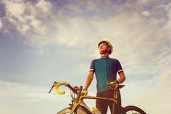 Конец вверх мужчины велосипедиста стоя с велосипедом дороги на заходе солнца, стоковое фото rf