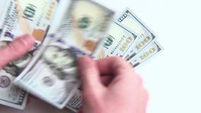 Конец-вверх мужчины вручает подсчитывать 10 100 долларовые банкноты Тысяча долларов на белой предпосылке Богатство и видеоматериал