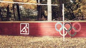 Конец вверх на белых знаке или значке велосипеда и покрашенный знак олимпийских колец на коричневое деревянном обнести общественн Стоковые Фотографии RF